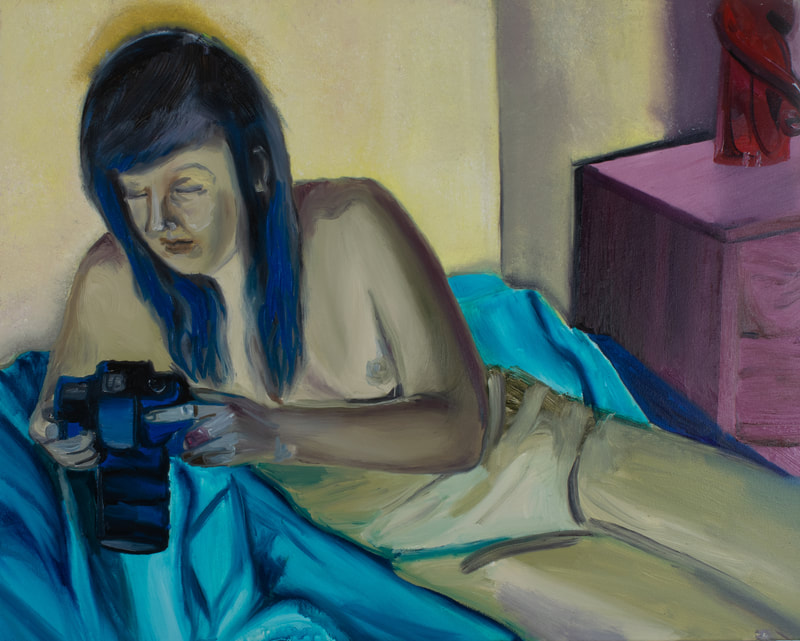 Olive green femme nude figure repose on blue bed gazing upon a hand held camera.